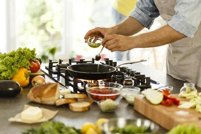 Escena de cocinando con aove. Aceite de oliva virgen extra. AOVE